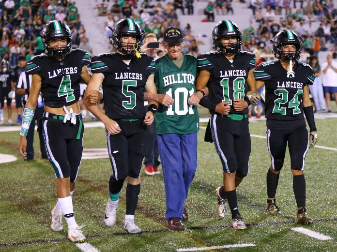 Former Hilltop High School teacher and World War II veteran Tom Rice (101) accompanies current Lancers Marko Aki (4), Gage Scruggs (5), Javin Deanda (18) and Tony Candelaria (24) during last Friday's pre-game recognition ceremony. Photo by Jon Bigornia (Star News)